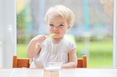 Girl eating delicious yogurt