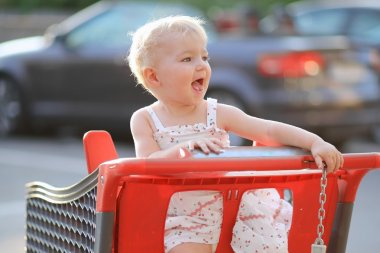 Baby girl sitting in red shopping cart