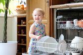 Fényképek mosolygó, szőke kisgyermek lány a konyhában, figyelembe véve a mosógép lemezek segít