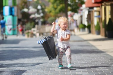 Cute baby girl standing or walking in the middle of the street in outlet village during sales with black shopping bag in her hands, crowd of people in the background