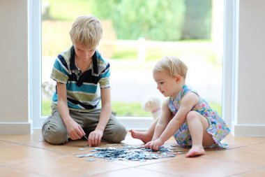 Girl playing puzzles with her brother