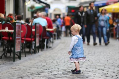 Baby girl standing on a busy crowded street