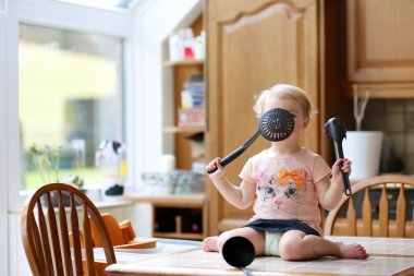 Girl playing with ladle and skimmer sitting on the table