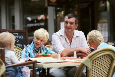 Father with three children having fun in cafe
