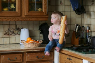 Girl sitting on the working surface eating baguette