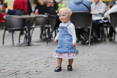 Baby girl standing next to chair of street cafe