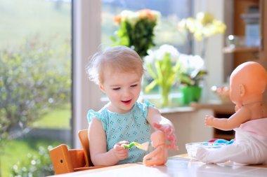 Girl feeding with yogurt her dolls
