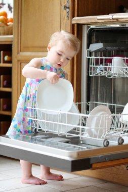 Girl taking plates out of dish washing machine