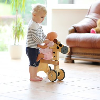Baby girl playing with doll and wooden wheeled horse