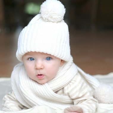 Baby in white knitted hat and scarf