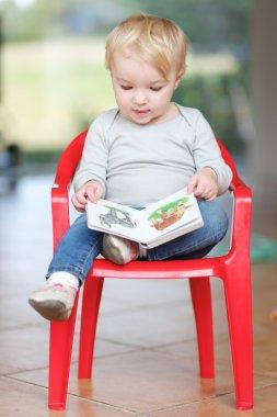 Baby girl reading children book about animals