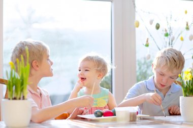 Group of cute children from one family, two twin brothers and their little toddler sister, decorating and painting Easter eggs sitting together in the kitchen on a sunny day. Selective focus on girl.
