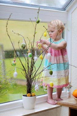 Adorable little blonde toddler girl decorating with Easter eggs cherry tree branches standing in the kitchen next a window with garden view