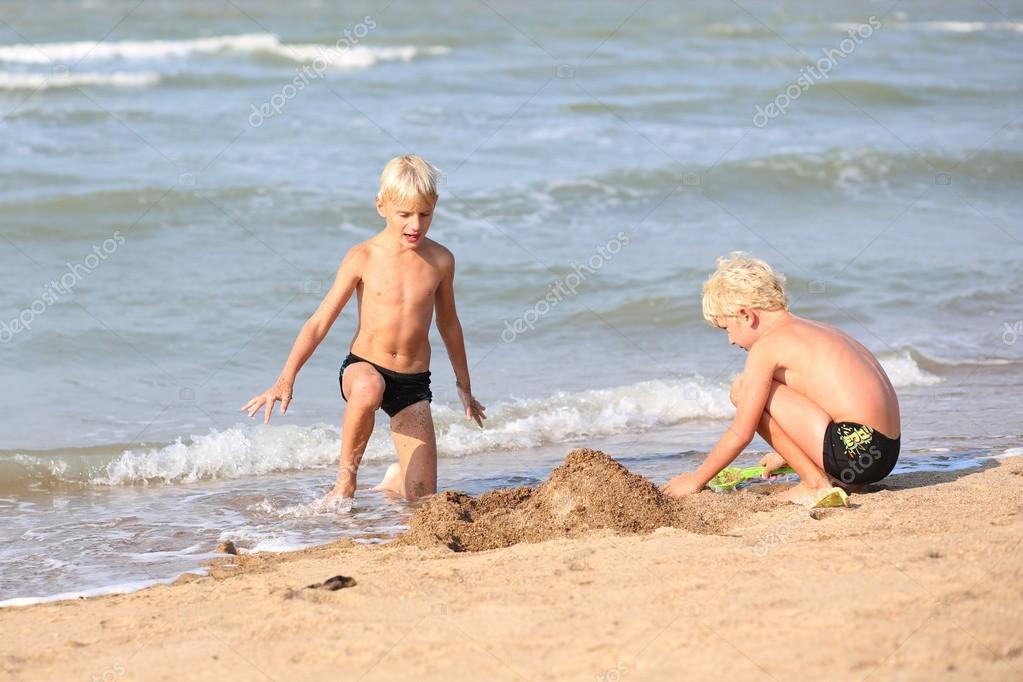 Twins brothers building sand castles