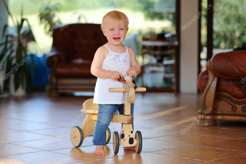 a7e5206f58d Adorable little baby girl learning to balance on her first bike, a wooden  horse on wheels. She is standing barefoot on tiles floor inside a house —  Photo by ...