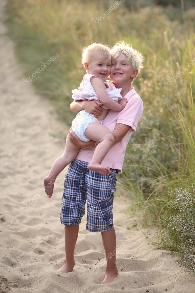 Brother with his baby sister on the beach
