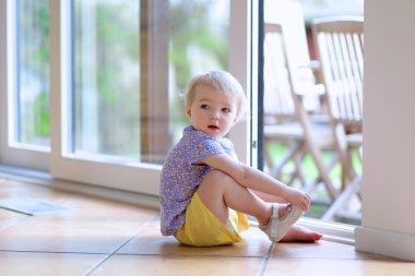 Girl  putting on her shoe sitting on floor