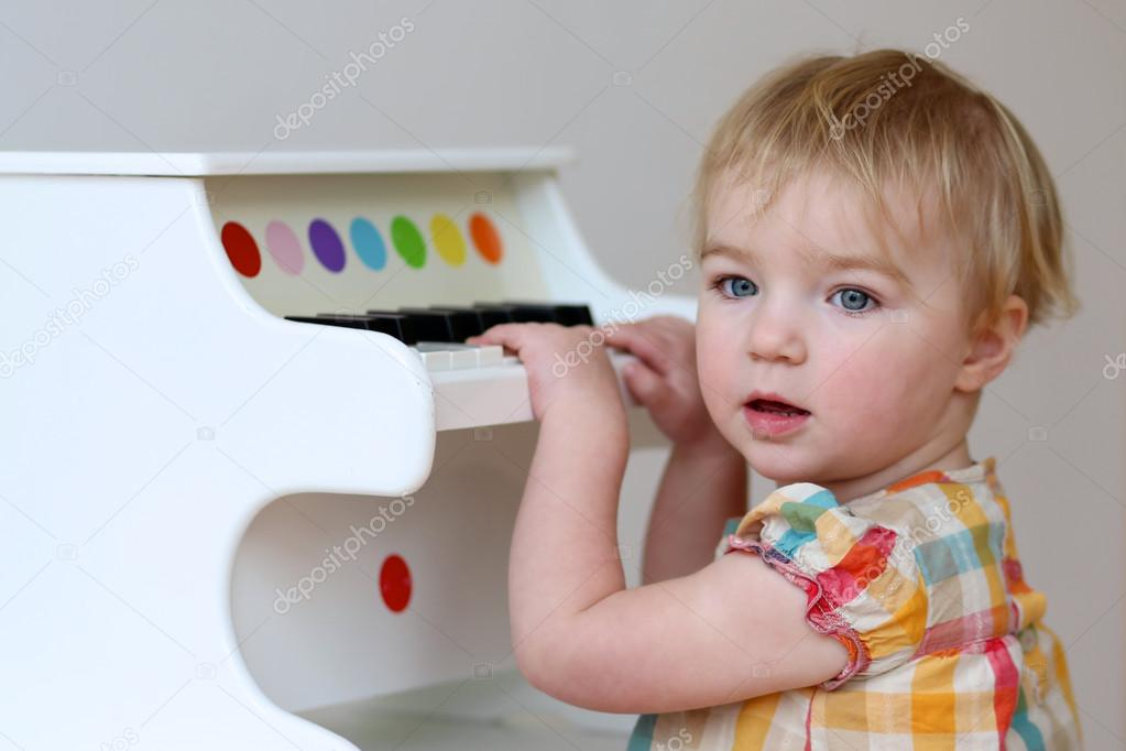 Girl learning to play on piano toy