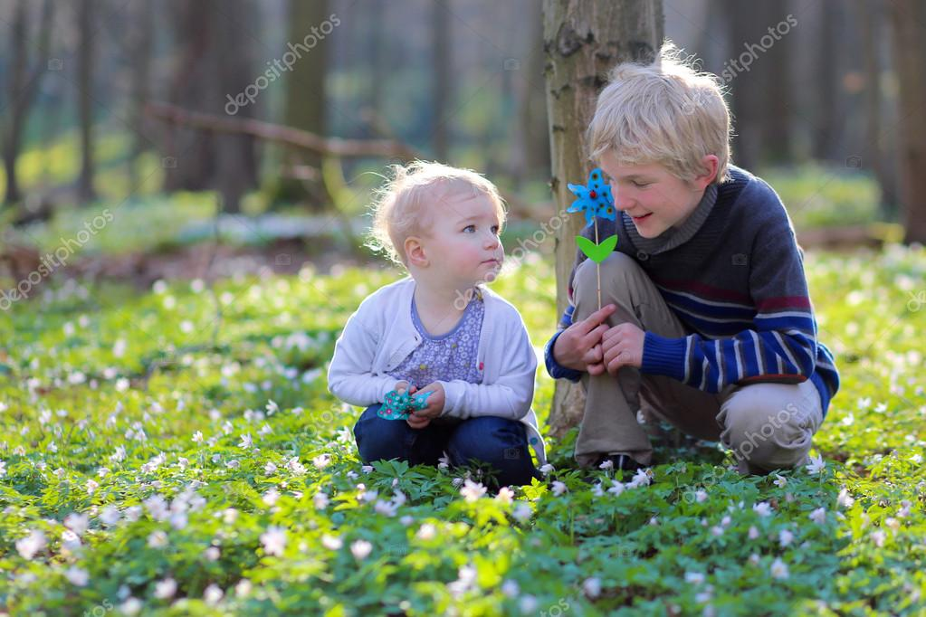 Boy with his toddler sister playing together in the forest