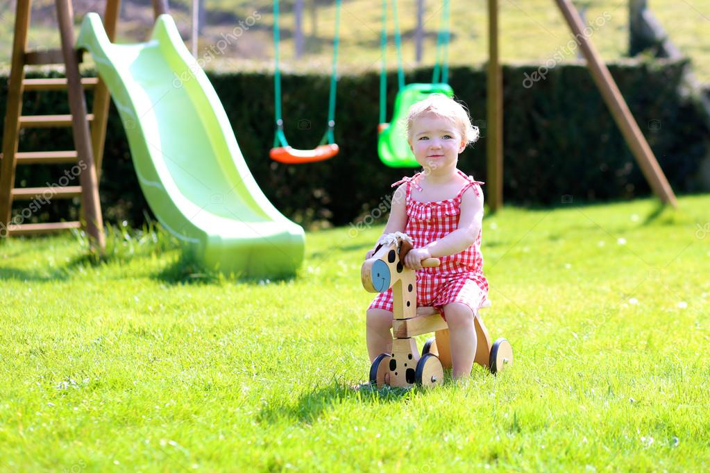 Cute blonde toddler girl riding wooden horse in summer garden