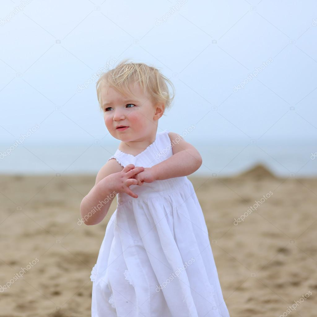 Portrait of beautiful toddler girl in white dress walking on the beach