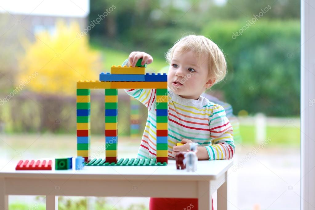 Happy toddler girl playing with colorful blocks indoors