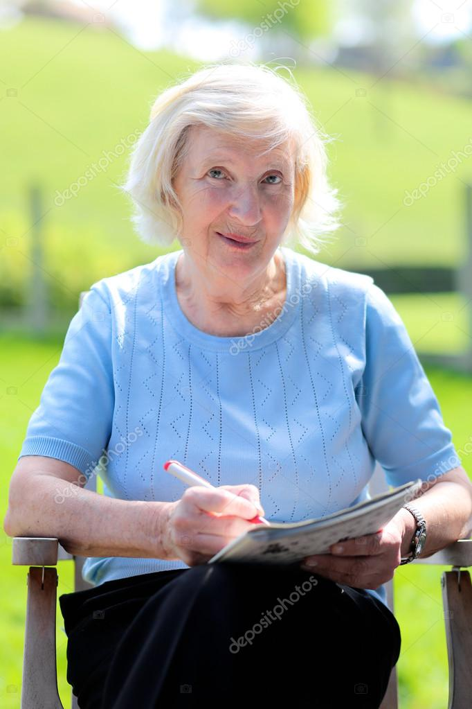 Happy senior woman relaxing outdoors sitting in the garden wooden chair reading newspaper and solving puzzles
