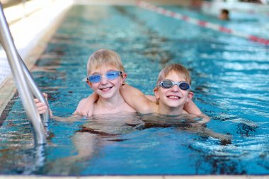 Twin boys having fun in the pool