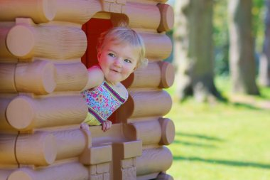 Cute toddler girl playing in playhouse