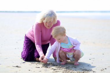 Happy grandmother playing with her granddaughter on the beach