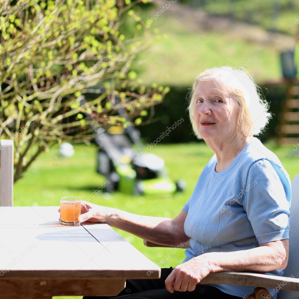Happy senior woman relaxing in summer garden
