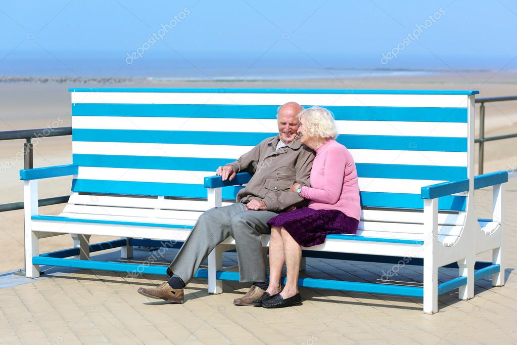 Happy senior couple relaxing on the promenade sitting on the bench
