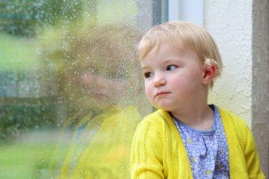 Little child looking through window