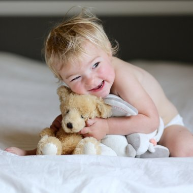 Cute toddler girl playing in bed with her teddy bear