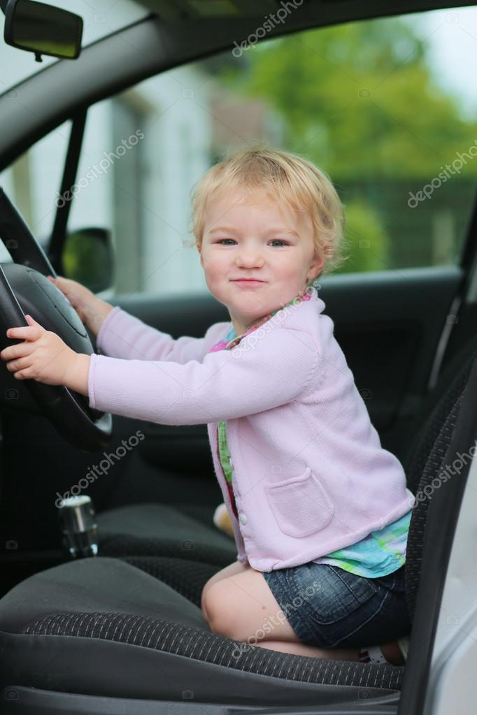 Happy Little Child Funny Blonde Toddler Girl Sitting On Her Knees Inside Of The Car Driver Seat Holding Steering Wheel Photo By CroMary
