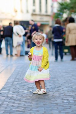 Happy little girl eating ice-cream in the center of the city
