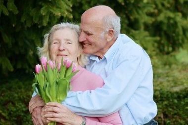 Loving senior couple with bouquet of pink tulips