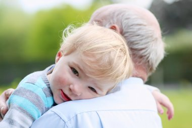 Cute little child comforting on the shoulder of grandfather