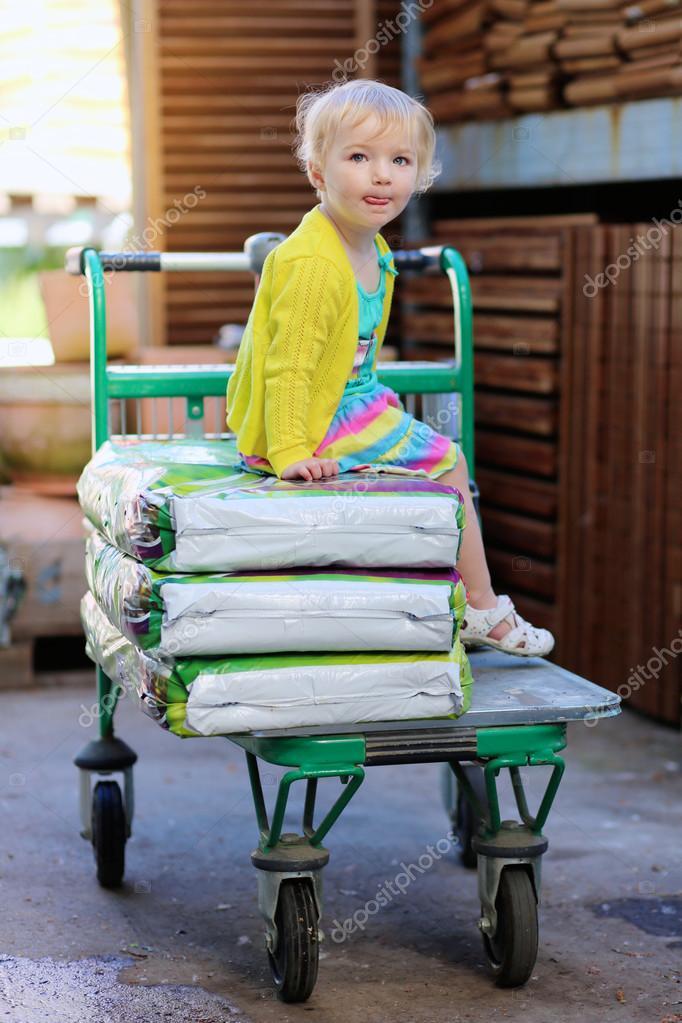 c274c482891 Χαριτωμένο μικρό παιδί, ξανθιά νήπιο σγουρά κορίτσι, συνεδρίαση στο ψώνια  άμαξα πάνω από τις σακούλες με το χώμα ή το λίπασμα στην αποθήκη στο mall  μεγάλα ...