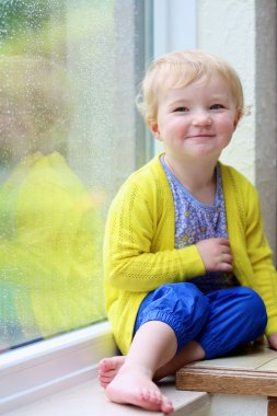 Cute little girl looking out of rainy window