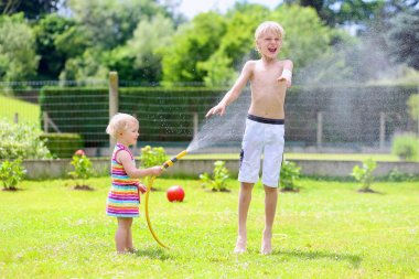 Brother and sister playing in the garden with watering hose