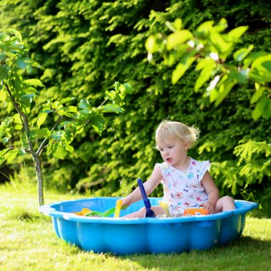 Happy little girl playing with sandbox outdoors  on a sunny summer day
