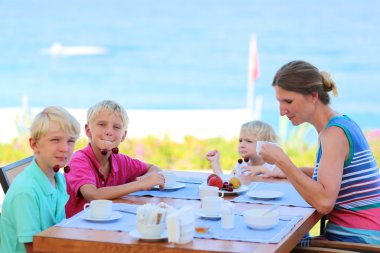 Family of four having healthy breakfast in outdoors cafe