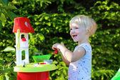 Fotografie šťastný batole dívka hraje s hračkou kuchyně venku