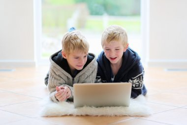Two school boys working with laptop lying on the floor