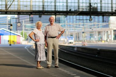 Senior couple waiting for train in railway station