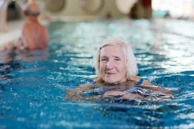 Happy senior woman swimming in the pool