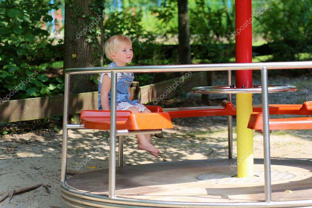 Adorable toddler girl playing in summer park