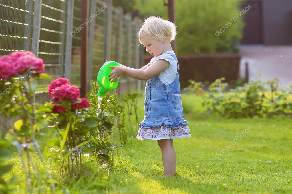 Cute toddler girl watering flowers in the garden