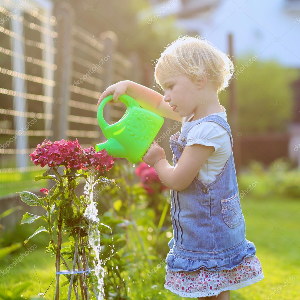 Cute toddler girl watering flowers in the garden